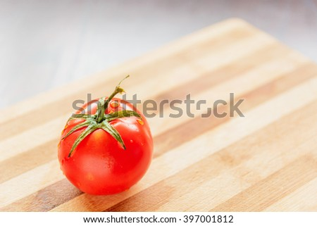 large and red tomato with green leaves on a bamboo board