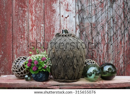 Large antique glass wine bottle wrapped in textile and netting, used as decoration together with old glass buoys. Photographed at Blomsoya, Nordland, Norway. - stock photo