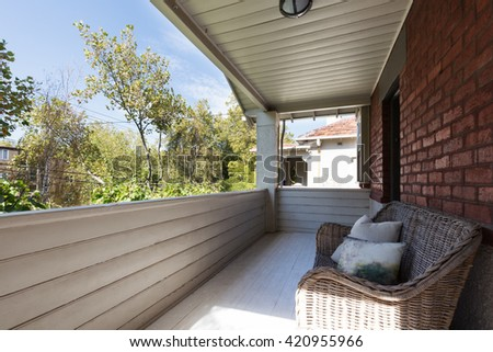 Large apartment balcony with cane outdoor seating and wood panelling - stock photo