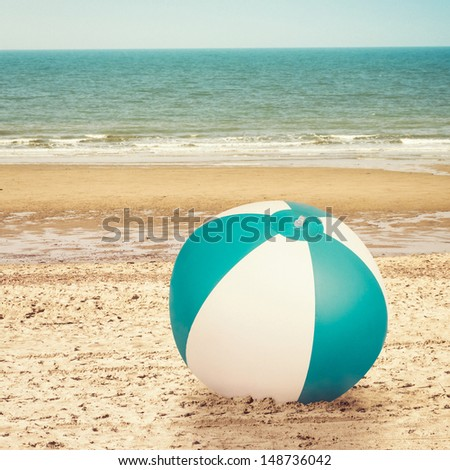 Large beachball on beach with ocean in background - stock photo