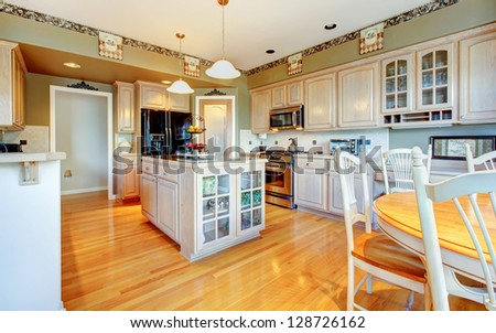Large beautiful white kitchen with hardwood floor and green walls.