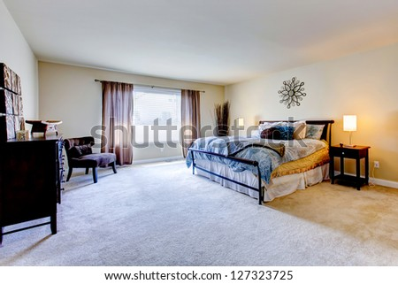 Large bedroom interior with beige carpet and black bed.