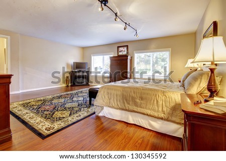 Large bedroom with hardwood floor and two dressers. - stock photo