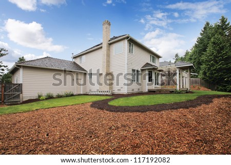 Large beige house with empty backyard during spring with mulch and grass. - stock photo