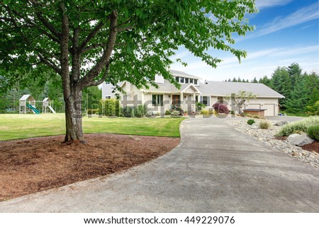 Large beige house with white trim, and well kept lawn, along with three garage spaces and playground at the back yard - stock photo