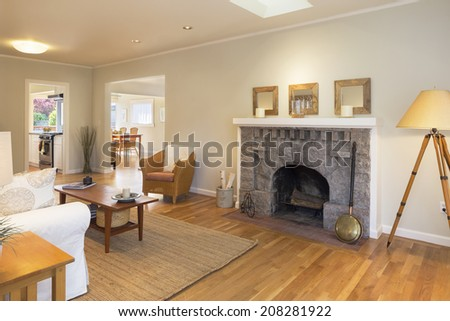 Large beige living room with skylight, recessed lighting, and fireplace adjacent to kitchen and dining room.  - stock photo