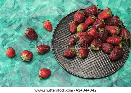 Large berry laid out on a black iron plate - stock photo