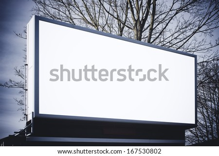 Large billboard in winter with tree behind - stock photo