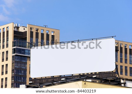 Large blank billboard on a building roof in the city downtown - stock photo