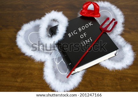 Large book labeled Big Book Of Sins on desktop with angel wings and halo, devil horns and pitch fork - stock photo