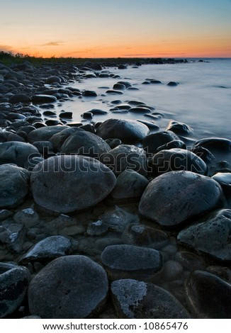 Large boulders washed by waves lit by the orange sky - stock photo
