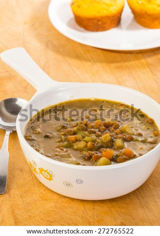 Large bowl of organic lentil and vegetable soup against wooden surface with cornbread.  Vertical format. - stock photo