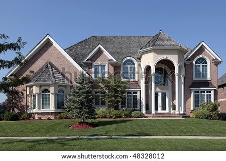 Large brick home in suburbs with columned entryway