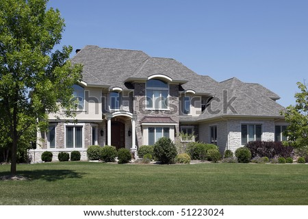 Large brick home with arched entry and cedar roof - stock photo