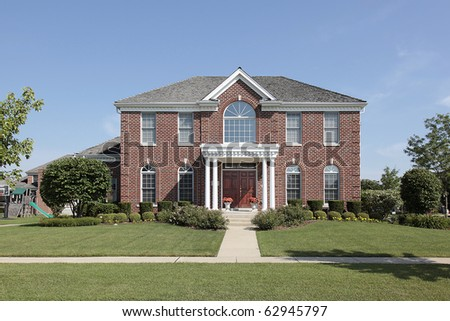 Large brick home with white columns and front balcony