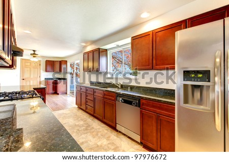 Large bright kitchen with dark cherry cabinets and stainless steal appliances. - stock photo