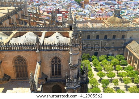 Large building and orange trees of the cloister of the Cathedral of Saint Mary of the See (Seville Cathedral) in Seville, Andalusia, Spain - stock photo