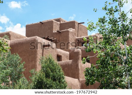 Large building with typical brown color adobe walls and architecture in Santa Fe, New Mexico, USA/Santa Fe, New Mexico, Architectural Style/Tall and big adobe-type structure on sunny day - stock photo