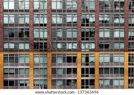 Large Building With Windows on a Brick And Yellow Wall Square Elevation Texture - stock photo
