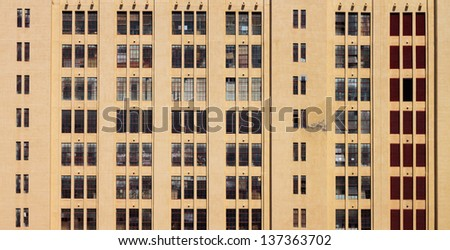 Large Building Yellow Wall with Windows Square Elevation Texture - stock photo