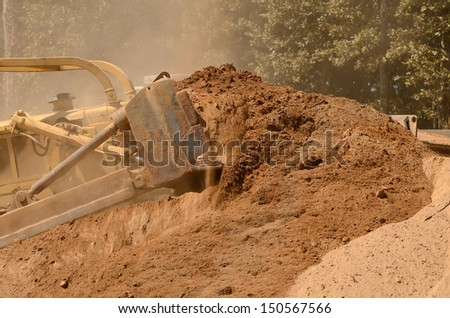 Large bulldozer excavating top soil for later use on a new commercial construction development project