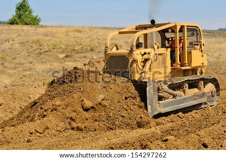 Large bulldozer moving rock and soil for a fill lift at a new commercial development road construction project