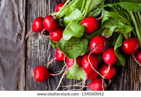 large bunch of fresh radish on dark boards, closeup - stock photo