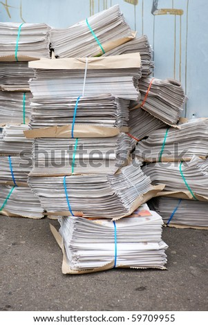 Large Bundles of newspapers stacked by a graffittied wall in an urban setting - stock photo