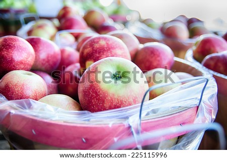 Large bushel basket full of fresh locally grown red apples at local farmers market - stock photo
