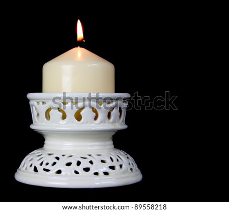 Large candle in an ornate ceramic holder