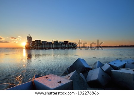 Large cargo container ship sailing against the sunset . Riga, Latvia - stock photo