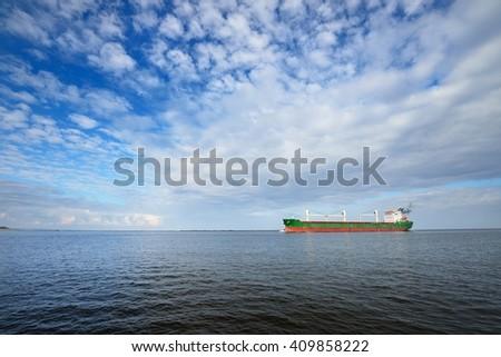 Large cargo ship (Bulk carrier) sailing in a bright sunny day. Riga, Latvia - stock photo