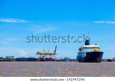 large cargo ship. Moored in the river. Large industrial port with freight.
