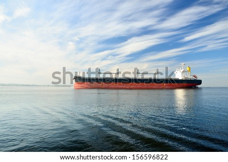 Large cargo ship sailing in still water - stock photo