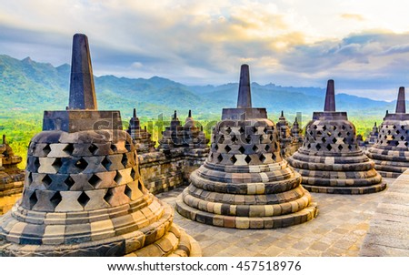 Large carved stone bells at the apex of the worlds largest 9th century Buddhist temple. The temple is also listed as a world heritage site. In the background is mountains covered lush green foliage.