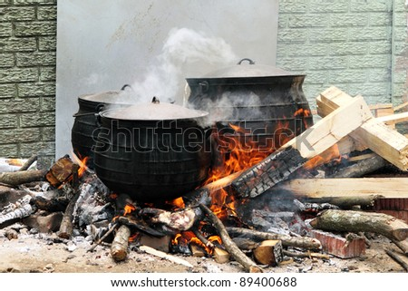 Large Cast Iron pots on wood fire with flames and steam - stock photo