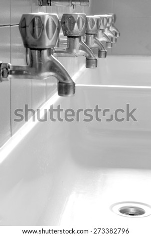 large ceramic sink with many taps in the school