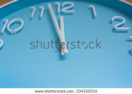 large clock blue face on wood background.