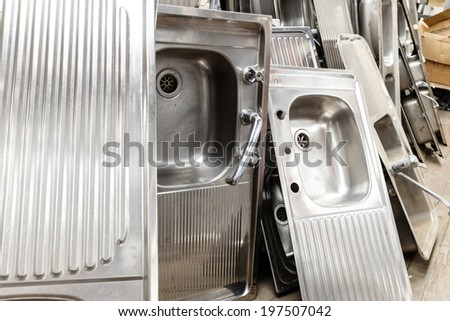Large collection of silver kitchen sinks - stock photo