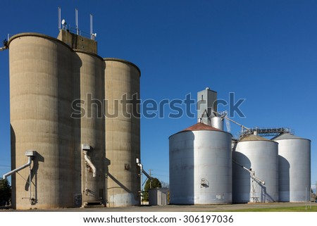 Large concrete and steel silos on blue sky. - stock photo