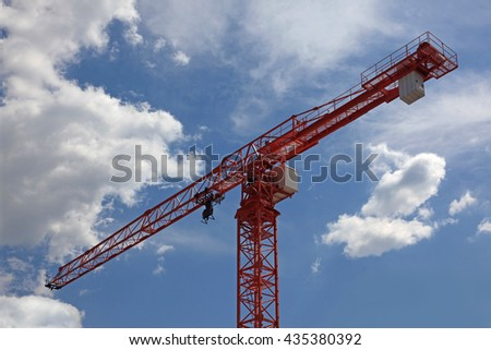 large construction crane against a blue sky with clouds - stock photo