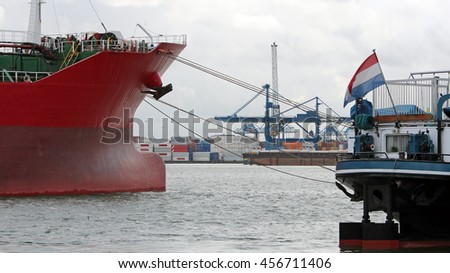 Large Container Ship Moored in a Harbor. Cranes and cargo containers alongside container ships moored at commercial dock. Industrial container freight trade port scene. - stock photo