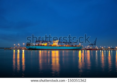 Large container ship on loading in the port of Gdansk, Poland. - stock photo