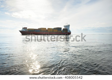 Large container ship sailing in still sea water - stock photo