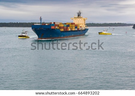 Large container ship with pilot boats