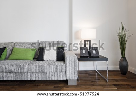large contemporary designer sofa with side table and reading lamp - stock photo