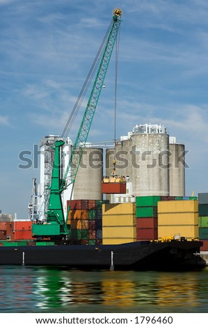 Large crane loading a ship with containers at Antwerp port - stock photo