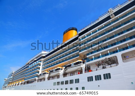 Large cruise ship with yellow funnel and blue balcony rise to blue sky - stock photo