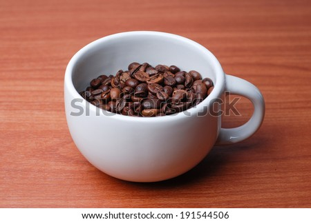 Large Cup Full Of Coffee Bean on brown wooden desk