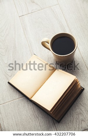 Large cup of coffee and open book. Education, hobby, drink.
